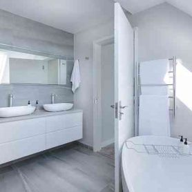 foto witte badkamer met betonlook vloer en een wit bad