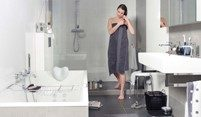 stock foto vrouw in witte badkamer met zwart stenen vloer